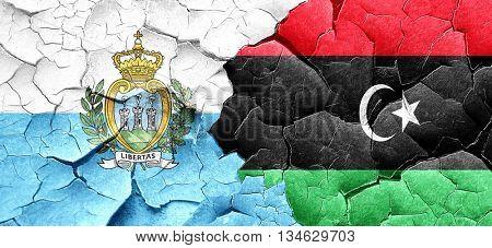 san marino flag with Libya flag on a grunge cracked wall