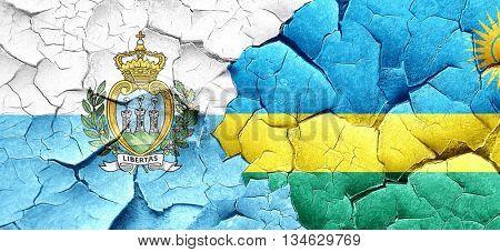 san marino flag with rwanda flag on a grunge cracked wall