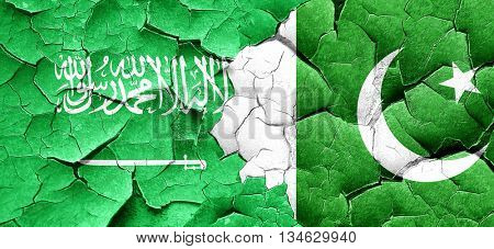 Saudi Arabia flag with Pakistan flag on a grunge cracked wall