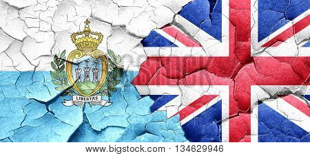 san marino flag with Great Britain flag on a grunge cracked wall