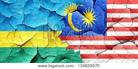 Rwanda flag with Malaysia flag on a grunge cracked wall
