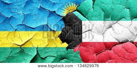 Rwanda flag with Kuwait flag on a grunge cracked wall