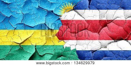 Rwanda flag with Costa Rica flag on a grunge cracked wall