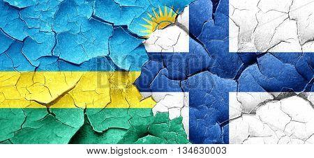Rwanda flag with Finland flag on a grunge cracked wall