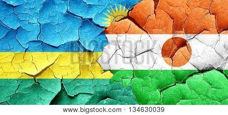 Rwanda flag with Niger flag on a grunge cracked wall