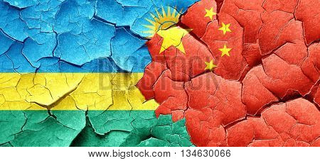 Rwanda flag with China flag on a grunge cracked wall