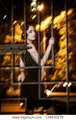 Emotions. Pretty woman posing in cage outdoors at night