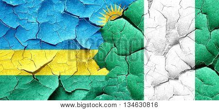 Rwanda flag with Nigeria flag on a grunge cracked wall