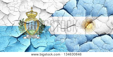 san marino flag with Argentine flag on a grunge cracked wall