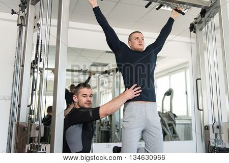 Man Doing Pull-ups Exercises With Gym Coach