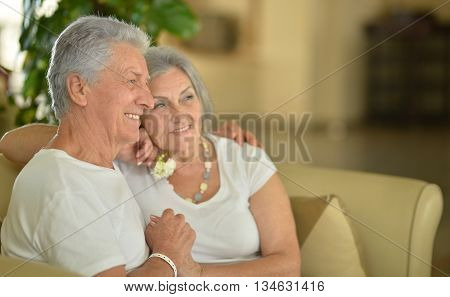Nice old couple went to a resort vacation, sitting in room on sofa