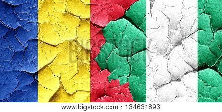 Romania flag with Nigeria flag on a grunge cracked wall