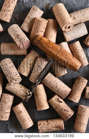 An antique corkscrew laying on a group of corks. Vertical format shot from a high angle.