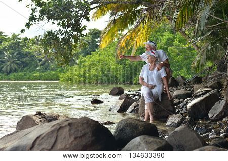 Happy elderly couple rest at tropical beach, man pointing by his hand
