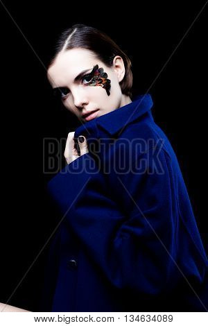 Young pretty woman face with false feather eyelashes fashion makeup  wearing blue coat