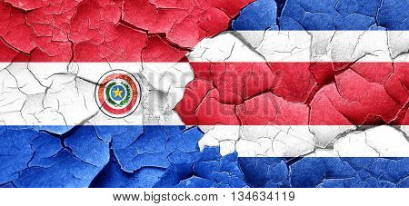 Paraguay flag with Costa Rica flag on a grunge cracked wall
