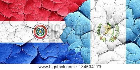 Paraguay flag with Guatemala flag on a grunge cracked wall