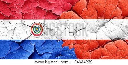 Paraguay flag with Austria flag on a grunge cracked wall