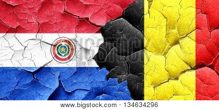 Paraguay flag with Belgium flag on a grunge cracked wall