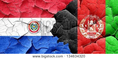 Paraguay flag with afghanistan flag on a grunge cracked wall
