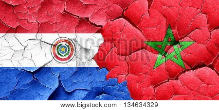 Paraguay flag with Morocco flag on a grunge cracked wall