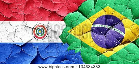 Paraguay flag with Brazil flag on a grunge cracked wall