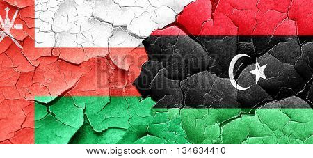 Oman flag with Libya flag on a grunge cracked wall