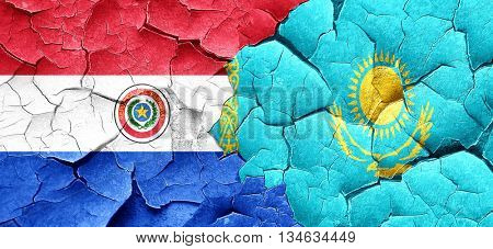 Paraguay flag with Kazakhstan flag on a grunge cracked wall