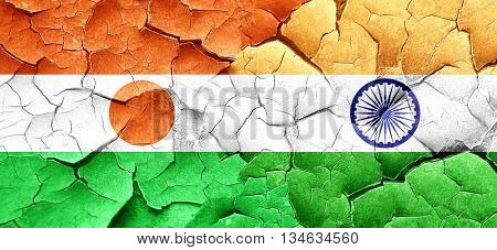 niger flag with India flag on a grunge cracked wall