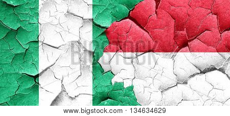 Nigeria flag with Indonesia flag on a grunge cracked wall