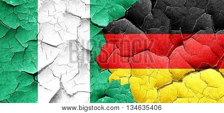 Nigeria flag with Germany flag on a grunge cracked wall