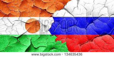niger flag with Russia flag on a grunge cracked wall
