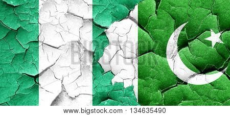 Nigeria flag with Pakistan flag on a grunge cracked wall