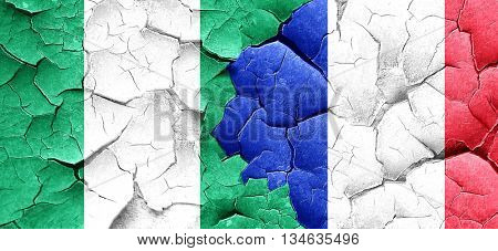 Nigeria flag with France flag on a grunge cracked wall