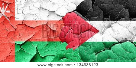 Oman flag with Palestine flag on a grunge cracked wall