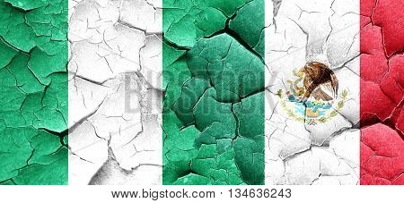 Nigeria flag with Mexico flag on a grunge cracked wall