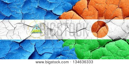 nicaragua flag with Niger flag on a grunge cracked wall