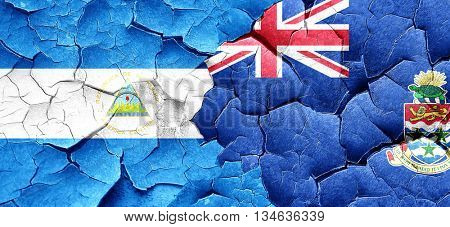 nicaragua flag with Cayman islands flag on a grunge cracked wall