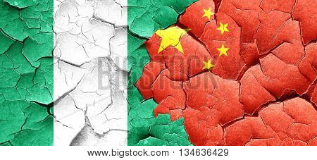 Nigeria flag with China flag on a grunge cracked wall