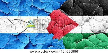 nicaragua flag with Palestine flag on a grunge cracked wall