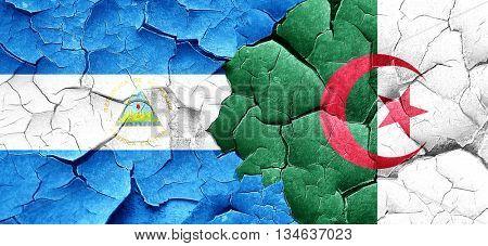 nicaragua flag with Algeria flag on a grunge cracked wall