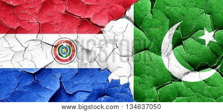 Paraguay flag with Pakistan flag on a grunge cracked wall
