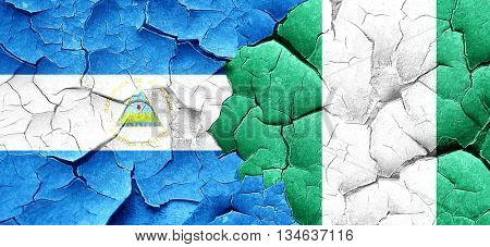 nicaragua flag with Nigeria flag on a grunge cracked wall