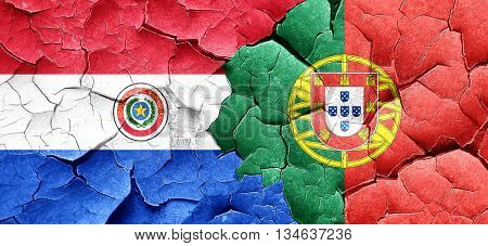 Paraguay flag with Portugal flag on a grunge cracked wall