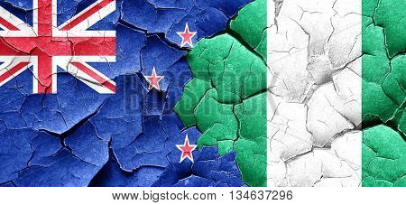 New zealand flag with Nigeria flag on a grunge cracked wall