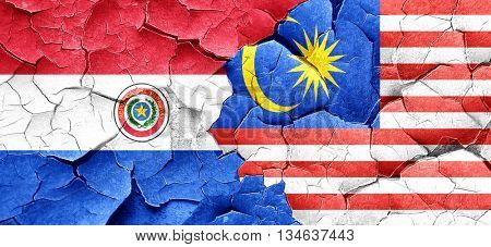 Paraguay flag with Malaysia flag on a grunge cracked wall