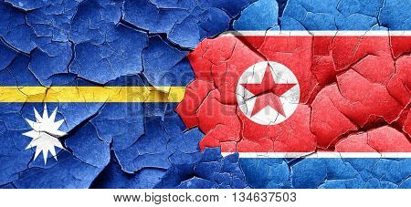 Nauru flag with North Korea flag on a grunge cracked wall