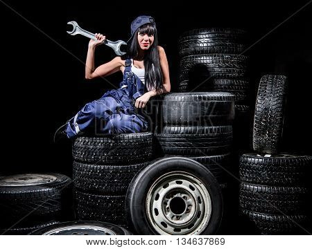 Sexy Young Woman Sitting On Wheels With A Big Wrench