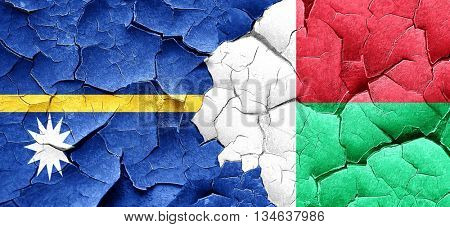 Nauru flag with Madagascar flag on a grunge cracked wall