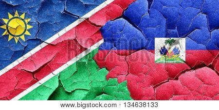 Namibia flag with Haiti flag on a grunge cracked wall